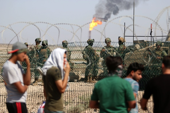 Protesters demonstrate as Iraqi soldiers stand guard oil fields in al-Qurnah, some 100 kilometers north of Basra, southern Iraq, on July 14, 2018. (HAIDAR MOHAMMED ALI/AFP/Getty Images)