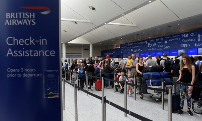 People line up at the British Airways check-in desk at Gatwick airport, England, on May 28, 2017. (Reuters/Hannah McKay)