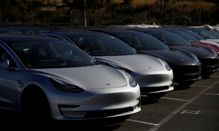 A row of new Tesla Model 3 electric vehicles is seen at a parking lot in Richmond, California, on June 22, 2018.   (Stephen Lam/Reuters)
