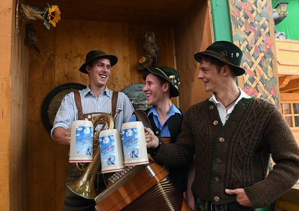 (L-R) Bavarian musicians Sepp, Andreas and Quirin wearing traditional Bavarian clothes pose with the new Oktoberfest beer mugs during a press conference in Munich, southern Germany, on Aug. 30, 2018. (Christof STACHE / AFP)
