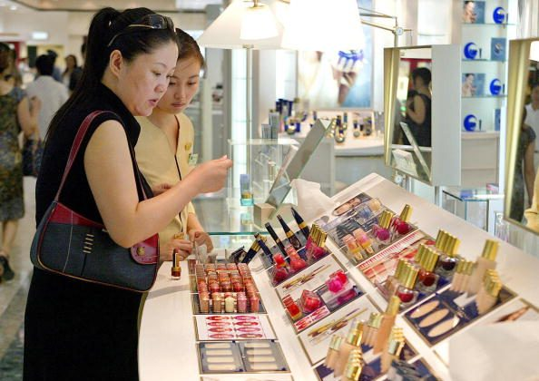 A woman checks out lipsticks at a department store in Shanghai on Aug. 16, 2004. (Liu Jin/AFP/Getty Images)