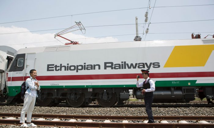 Chinese employees of the new railway which will link Addis Ababa to Djibouti take pictures in front of the Chinese-made Ethiopian trains in Addis Ababa, Ethiopia, on Sep. 24, 2016.