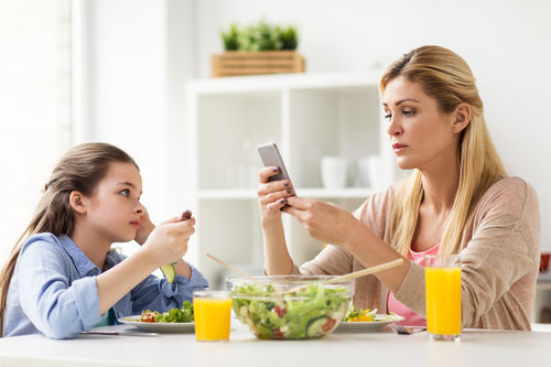 Parents who are absorbed with and distracted by their mobile devices tend to have less parent-child interaction and more conflict with their kids. (Shutterstock)