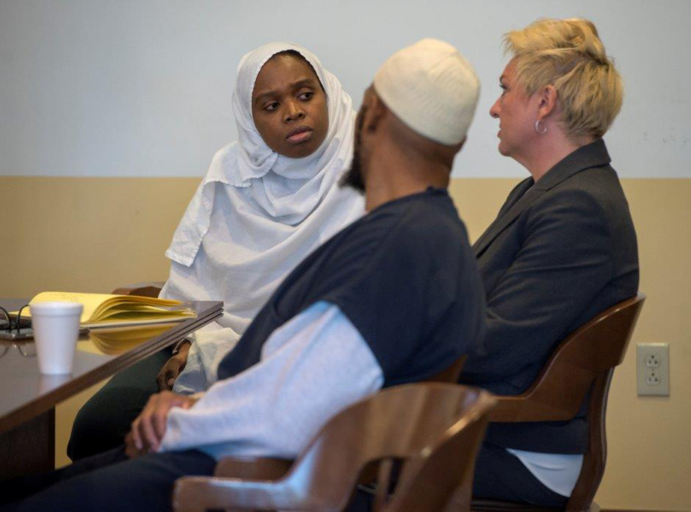 Jany Leveille (L to R) and Siraj Ibn Wahhaj talk to defense lawyer Kelly Golightley during a hearing in Taos District Court in Taos County