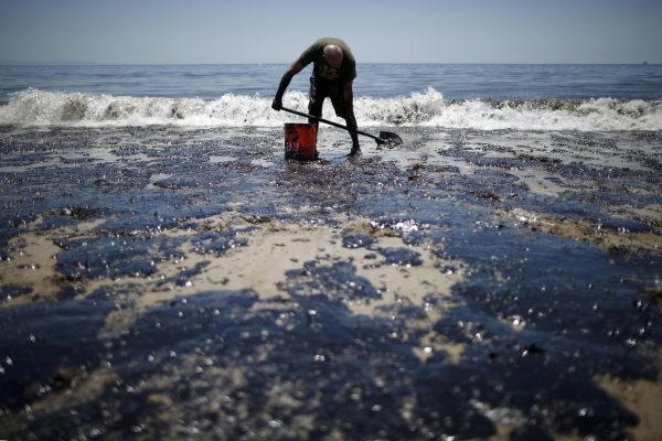 William McConnaughey, 56, who drove from San Diego to help shovel oil off the beach, stands in an oil slick in bare feet along the coast of Refugio State Beach