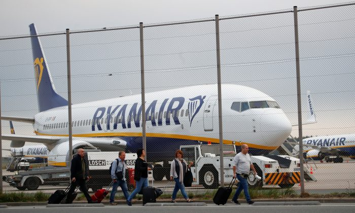Passengers walk in front of an aircraft of low-cost airliner Ryanair at Weeze Airport, near the German-Dutch border, during a strike of the airline's crews, protesting the slow progress in negotiating a collective labour agreement at Weeze airport, Germany, September 12, 2018. (Wolfgang Rattay/Reuters)