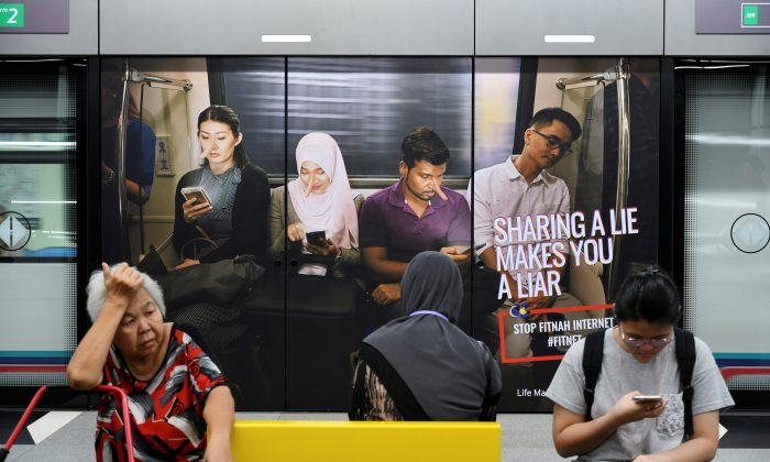 Commuters sit in front of an advertisement discouraging the dissemination of fake news, at a train station in Kuala Lumpur, Malaysia, on March 28, 2018. (Stringer/Reuters)