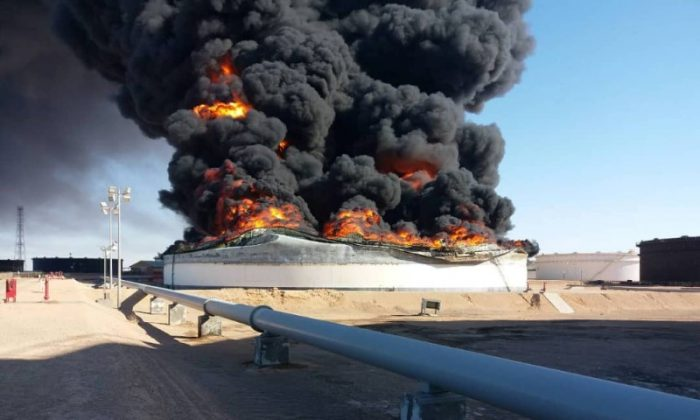 Smoke and flame rise from an oil storage tank that was set on fire amid fighting between rival factions at Ras Lanuf terminal, Libya in this handout picture released on June 18, 2018. (The National Oil Corporation/ Handout via Reuters)