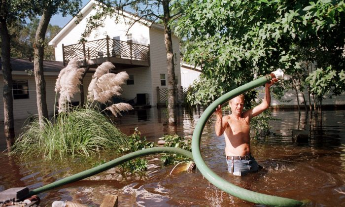 File photo showing a North Carolina resident trying to pump flood waters from around his home following heavy rains from Hurricane Floyd on 17 Sept. 1999 in Ocean Isle Beach, NC. Floyd killed over a dozen people, wreaked serious damage and triggered the largest peacetime evacuation ever undertaken in the United States. (Steve Schaefer/AFP/Getty Images)