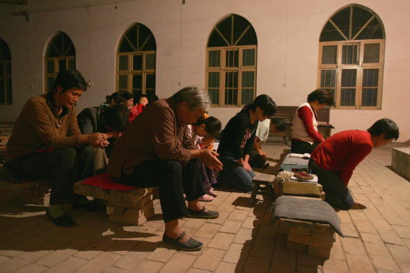 Christians pray during a mass at a village church in the outskirts of Yanshi City, Henan Province, on Oct. 6, 2006. (China Photos/Getty Images)