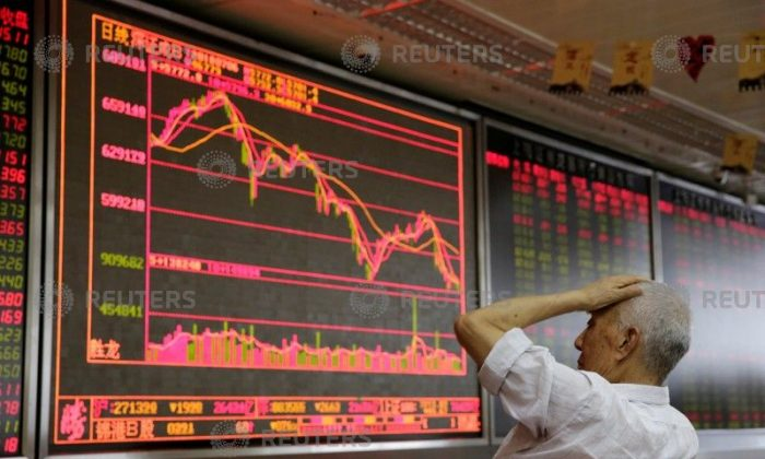 An investor looks at a board showing stock information at a brokerage office in Beijing on July 6, 2018. (Jason Lee/Reuters)