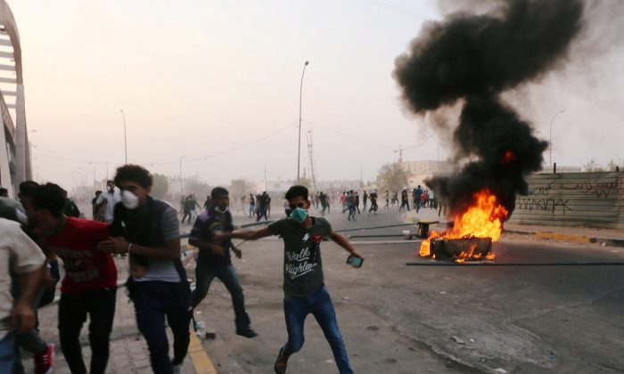 Iraqi protesters run during a protest near the building of the government office in Basra, Iraq, on Sept. 5, 2018. (Alaa al-Marjani/Reuters)