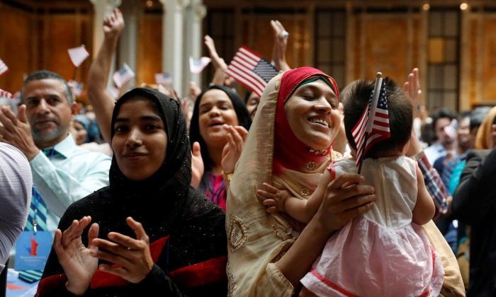 New citizens smile at a U.S. Citizenship and Immigration Services (USCIS) naturalization ceremony at the New York Public Library in Manhattan, New York, U.S., July 3, 2018.  (Shannon Stapleton/Reuters)