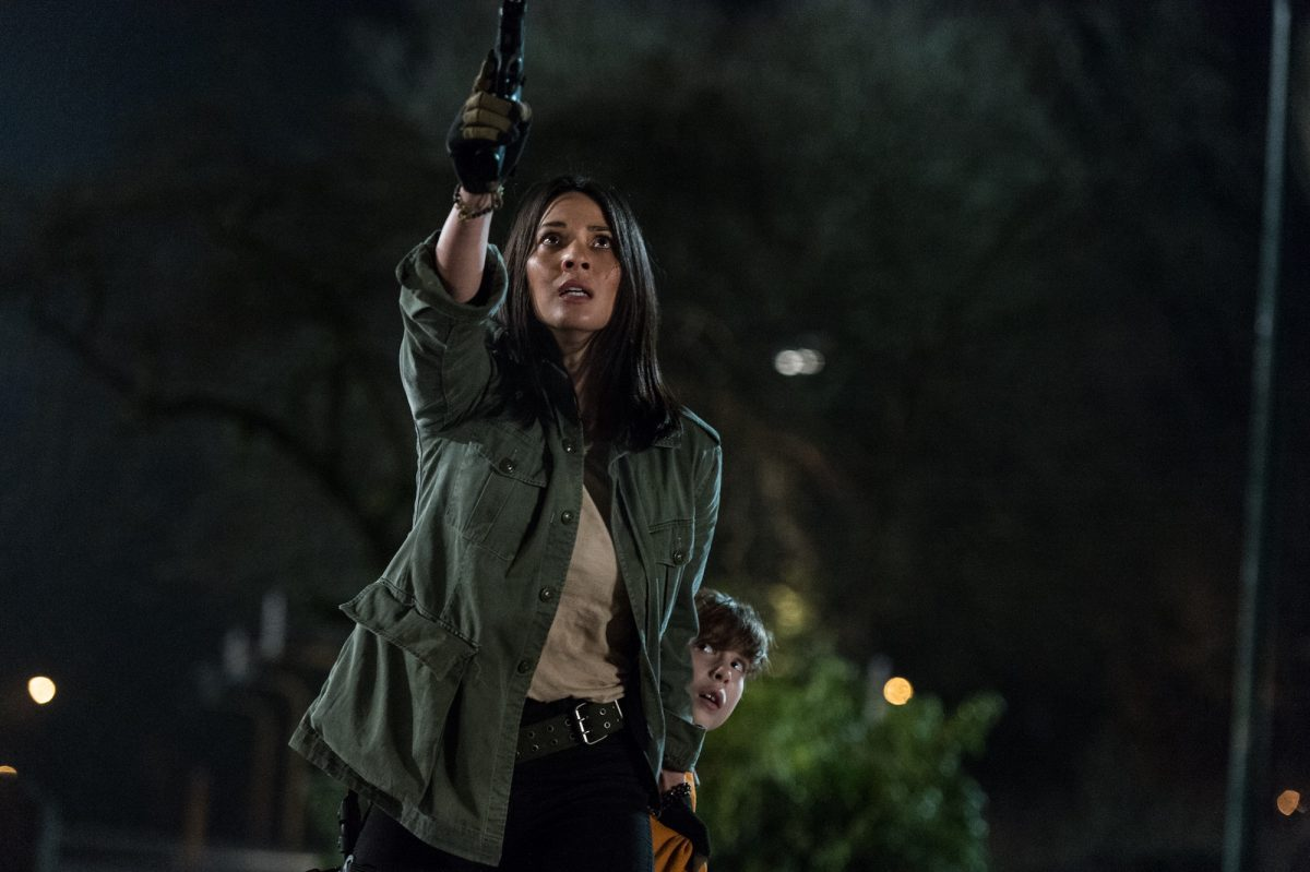 Olivia Munn points gun.