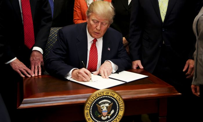 President Donald Trump signs an Executive Order calling for the review of the Waters of the United States Rule, in the Roosevelt Room of the White House in Washington on Feb. 28, 2017. (Aude Guerrucci-Pool/Getty Images)