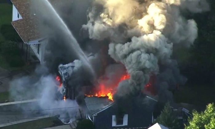 Flames consume the roof of a home in Lawrence, Mass, a suburb of Boston, on Sept. 13, 2018. (WCVB via AP)