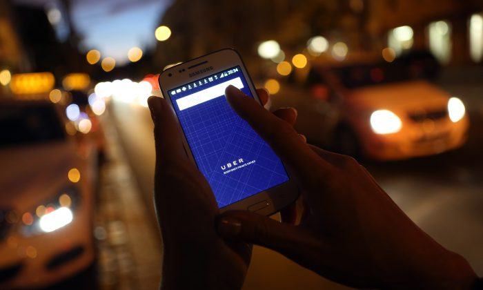 A woman uses the Uber app on a Samsung smartphone on Sept. 2, 2014. (Photo by Adam Berry/Getty Images)