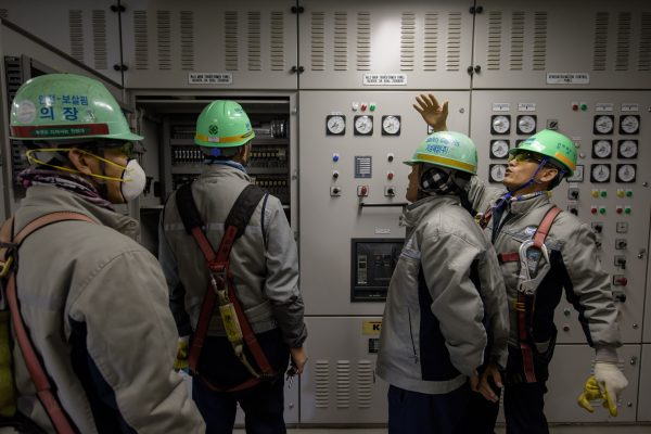 South Korean workers stand before instrument panels in the engine control room of an under-construction container ship at the Daewoo DSME shipyard in Okpo, south of Busan, on Dec. 3, 2014. (Ed Jones/AFP/Getty Images)