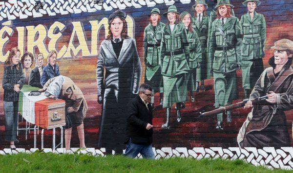 A man walks past a Republican mural