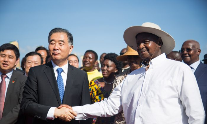 China's third vice prime minister, Wang Yang (L) and Uganda's President Yoweri Museveni (R) shake hands as they pose during the inauguration ceremony of the Chinese-funded 51-kilometer Expressway linking the capital city and the international airport in Entebbe, Uganda, on June 15, 2018. (SUMY SADURNI/AFP/Getty Images)
