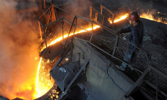 A worker monitors molten iron pouring into a furnace at a steel manufacturing plant in Hefei City, Anhui Province, China, on August 15, 2012. (Stringer/Reuters)