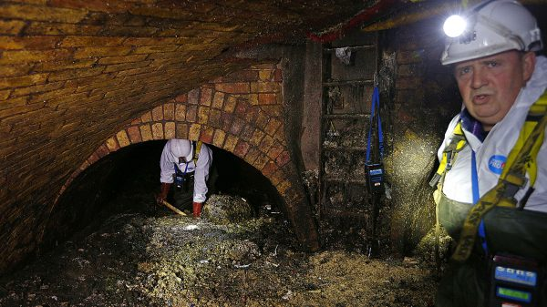 Sewer workers shovel up a fatberg under London