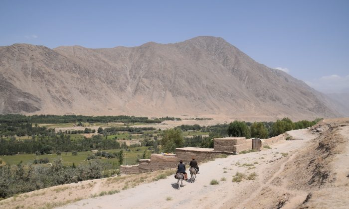 The front between government-held Bahorak and Taliban-controlled Warduj in Badakhshan province, Afghanistan, on Aug. 25, 2018. The bend on the dusty road (centre, right) and the white house (centre) at the foot of the mountain, roughly mark,where Taliban territory begins. (Franz J. Marty/Special to The Epoch Times)