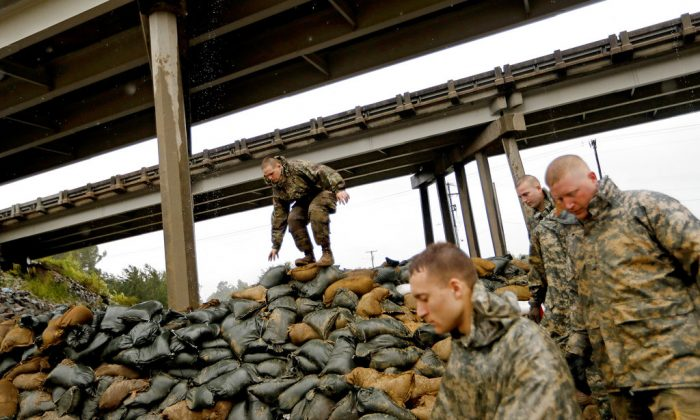 Members of the North Carolina National Guard finish stacking sand bags under a highway overpass near the Lumber River which is expected to flood from Hurricane Florence's rain in Lumberton, N.C., Friday, Sept. 14, 2018. (David Goldman/AP)