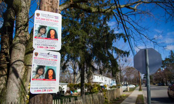A sign offering a reward for information about the murders of Nisa Mickens and Kayla Cuevas, near Brentwood High School in Brentwood, Suffolk County, N.Y., on March 29, 2017. (Samira Bouaou/The Epoch Times)