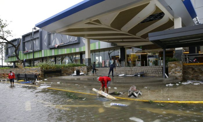 Workers clean up debris outside a mall that got partially damaged by strong winds from Typhoon Mangkhut as it barreled across Tuguegarao city in Cagayan province, northeastern Philippines on, Sept. 15, 2018. (AP Photo/Aaron Favila)