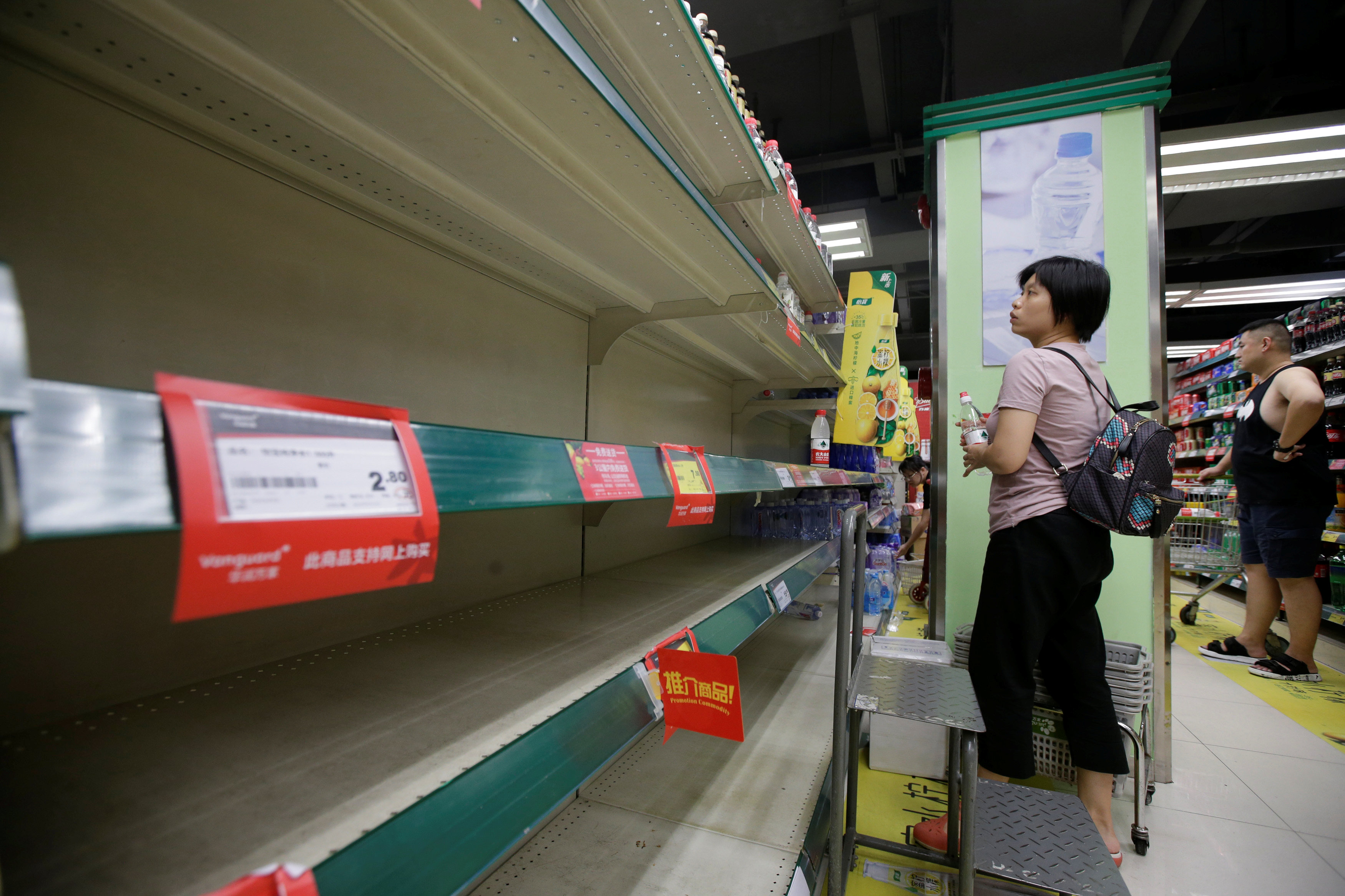 A local resident selects bottled water at a supermarket in preparation for Typhoon Mangkhut in Shenzhen