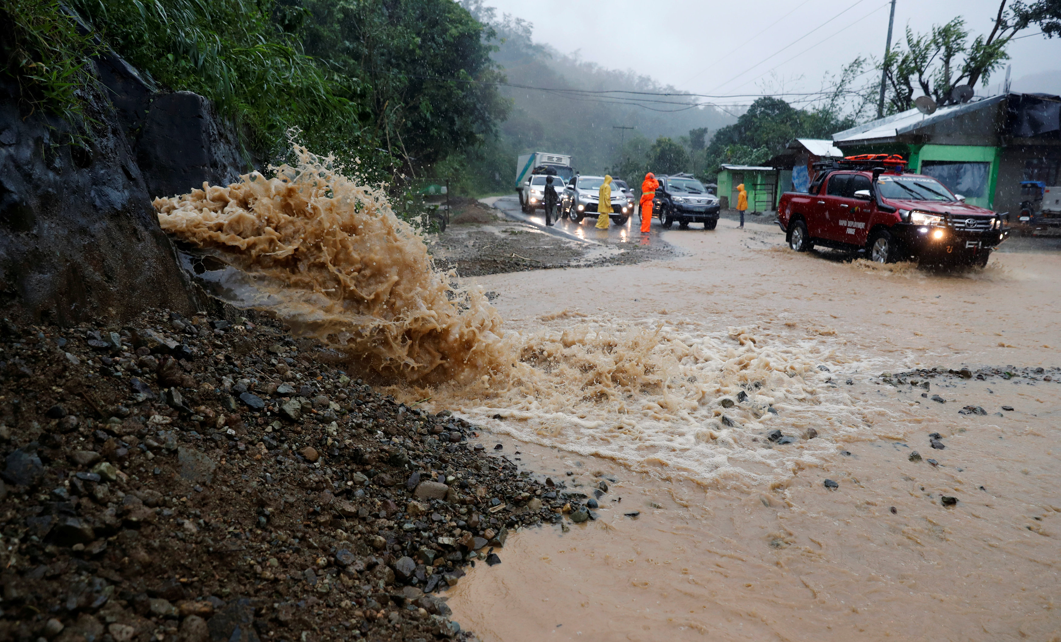 Motorists drive past a partially damaged road after Typhoon Mangkhut hit the main island of Luzon, in Carranglan, Nueva Ecija