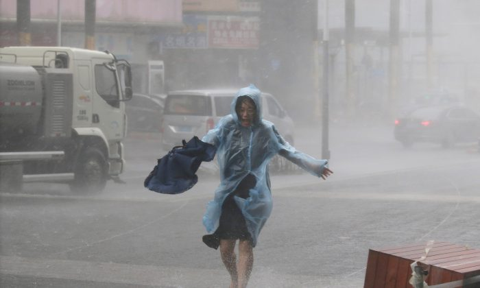 A woman runs in the rainstorm as Typhoon Mangkhut approaches, in Shenzhen City, Guangdong Province, China, on Sept. 16, 2018. (Reuters/Jason Lee)