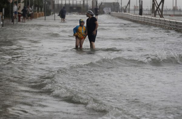 People walk through floodwaters