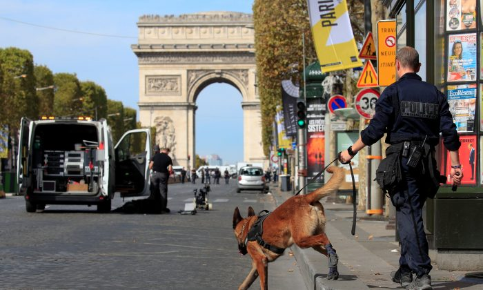 Paris police bomb squad and sniffing dog inspect a car in Champs Elysees avenue in Paris, France, on Sept. 16, 2018. (Gonzalo Fuentes/Reuters)