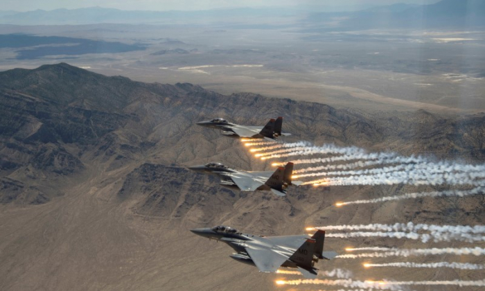 Three U.S. Air Force F-15E Strike Eagles,  from Mountain Home Air Force Base, Idaho, fire flares over the Utah Test and Training Range, west of Salt Lake CIty in Utah, on July 3, 2018.   (Reuters)