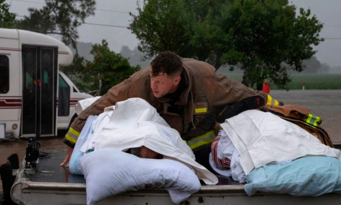 A Lumberton firefighter holds on to two nursing home patients as a member of the Cajun Navy drives his truck during the evacuation of a nursing home due to rising flood waters in Lumberton, North Carolina, on Sept. 15, 2018 in the wake of Hurricane Florence. (Alex Edelman / AFP/Getty Images)