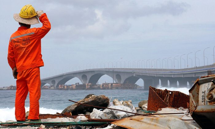 A construction worker looks on as the China-funded Sinamale bridge is seen in Male, Maldives on September 18, 2018. (Ashwa Faheem/Reuters)