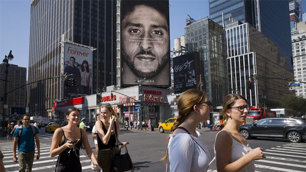 People walk by a Nike advertisement featuring Nike ambassador Colin Kaepernick, a former NFL football star, in New York City on Sept. 6, 2018. (Mark Lennihan/AP Photo)
