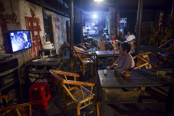An elderly waitress watching television at a teahouse in Chengdu City, Sichuan Province, on Sept. 11, 2016. (WANG ZHAO/AFP/Getty Images)