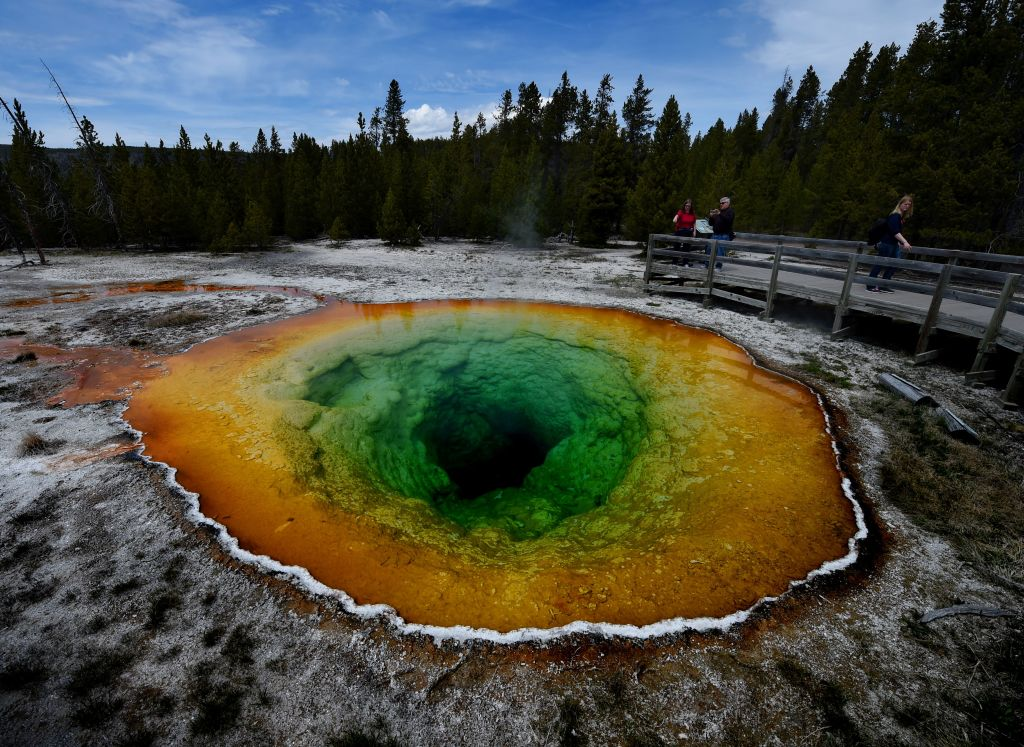 Tourists view the Morning Glory hot spring in the Upper Geyser Basin of Yellowstone National Park in Wyoming, on May 14, 2016. (MARK RALSTON/AFP/Getty Images)