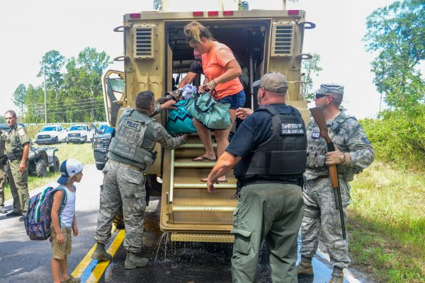 Relief crews help a person off a truck