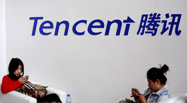 Visitors use their smartphones underneath the logo of Tencent at the Global Mobile Internet Conference in Beijing May 6, 2014. (Reuters/Kim Kyung-Hoon)