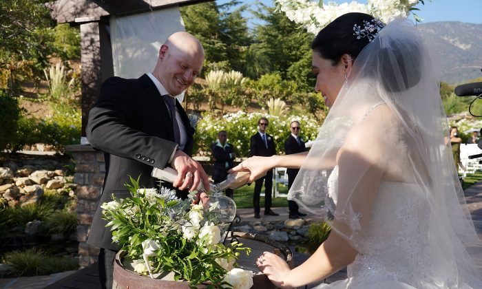 Stefany Ornelas and Alex Washer perform the unity sand ceremony during their wedding ceremony at Serendipity Garden in San Bernardino, California on Sept. 7, 2018. (JC Olivera/Getty Images for Stellar)