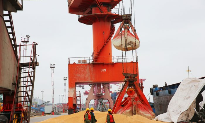 Workers walk past imported soybeans at a port in Nantong City, Jiangsu Province, on April 4, 2018. (AFP/Getty Images)