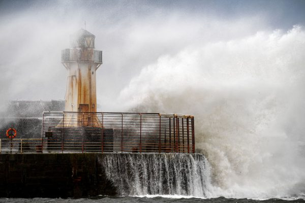 Waves crash against the harbor wall as Storm Ali hits land