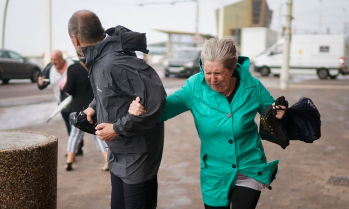 People struggle in the wind as Storm Ali hits land on Sept. 19, 2018, in Blackpool, northern England. (Christopher Furlong/Getty Images)