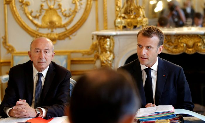 French President Emmanuel Macron sits next to Interior Minister Gerard Collomb at the Elysee Palace in Paris, France on Aug. 3, 2018. (Michel Euler/Pool via Reuters/File Photo)