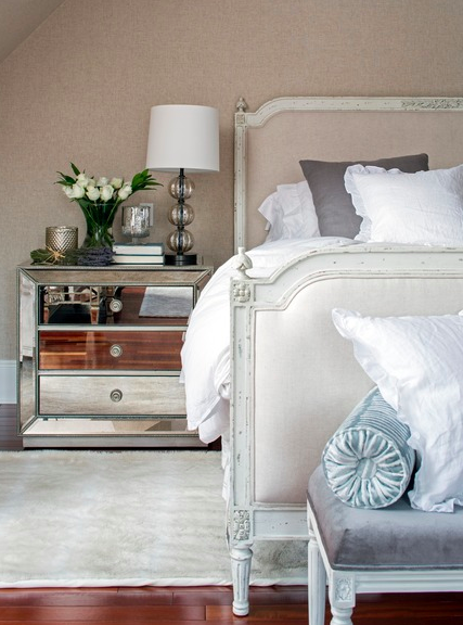 Mirrored accent furniture, such as the chic bedside table from Z Gallerie, gives the master bedroom a distinct deco feel.