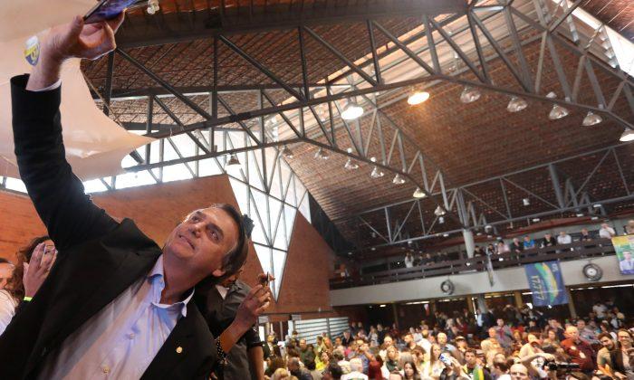 Presidential candidate Jair Bolsonaro takes a selfie as he attends a rallyin Porto Alegre, Brazil Aug. 30, 2018. (Diego Vara/Reuters)